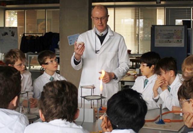 「寄宿学校 - Boarding school 理科の実験の授業風景。実演中の教師とそれを見つめる生徒達の様子(写真)」UK留学情報センター