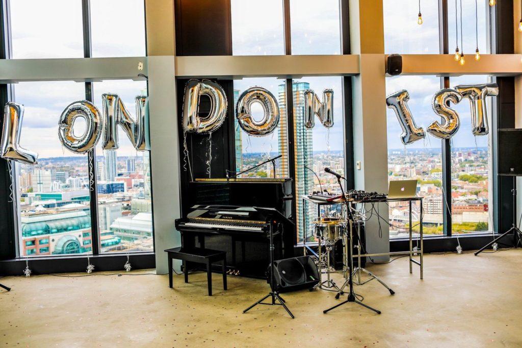 ホームステイ・寮・シェアハウス「LONDONIST室内の様子・・・窓際に掲げられたLONDONISTを形どったオーナメント、置かれたピアノ、スタンドマイク、モニター等」(写真)UK留学情報センター