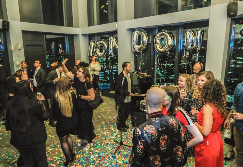 ホームステイ・寮・シェアハウス「LONDONIST室内の様子・・・窓際にLONDONISTを形どったオーナメントが掲げられ、ピアノ、スタンドマイク、モニター等が置かれたホールで学生達が集まってパーティーを楽しんでいる」(写真)UK留学情報センター