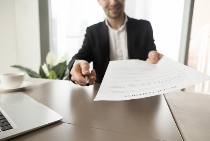 デスクで契約書を差し出す男性(写真)UK留学情報センター