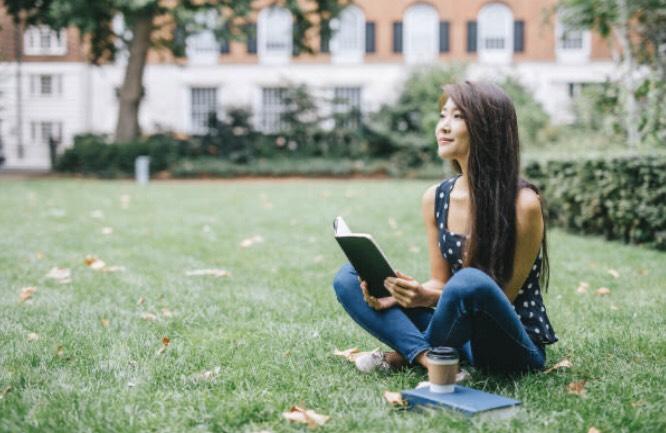 留学中に大学の前で何かを考えている女性(写真)UK留学情報センター