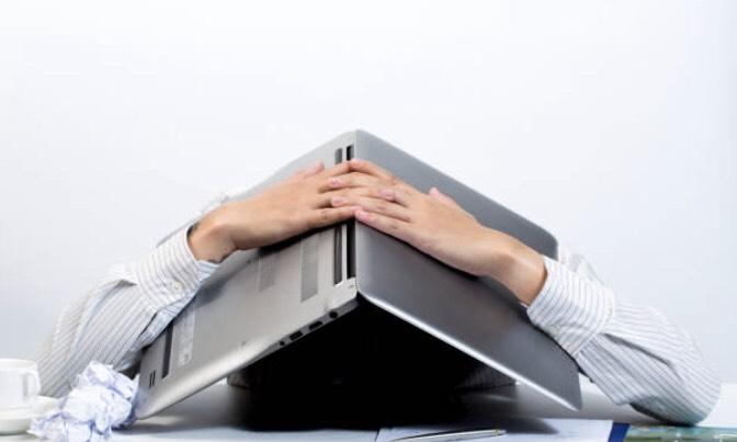 パソコンを頭に乗っけている男性
