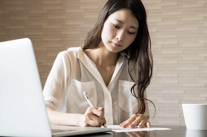 書類に記載している女性